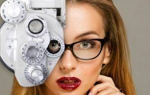 close up on blonde woman with red lips looking through eye exam technology while wearing eyeglasses